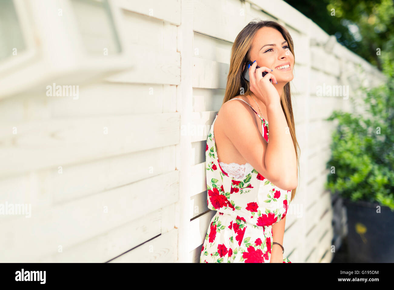 Beautiful young happy woman smiling during a phone call while leaning against a white wall - Stock Image