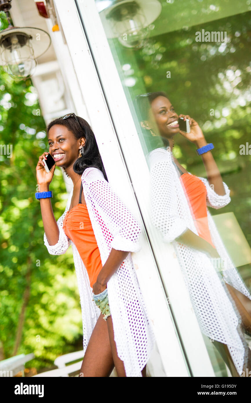 Beautiful black woman talking on phone and smiling during a summer day and her reflection showing on the window - Stock Image