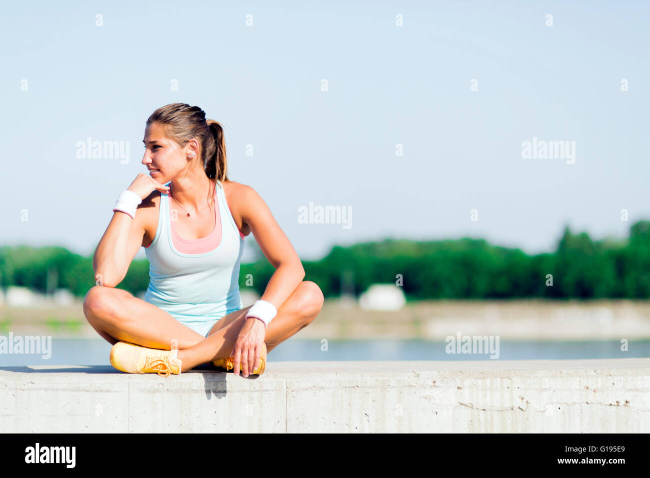 Young woman stretching and relaxing in the city before exercise - Stock Image