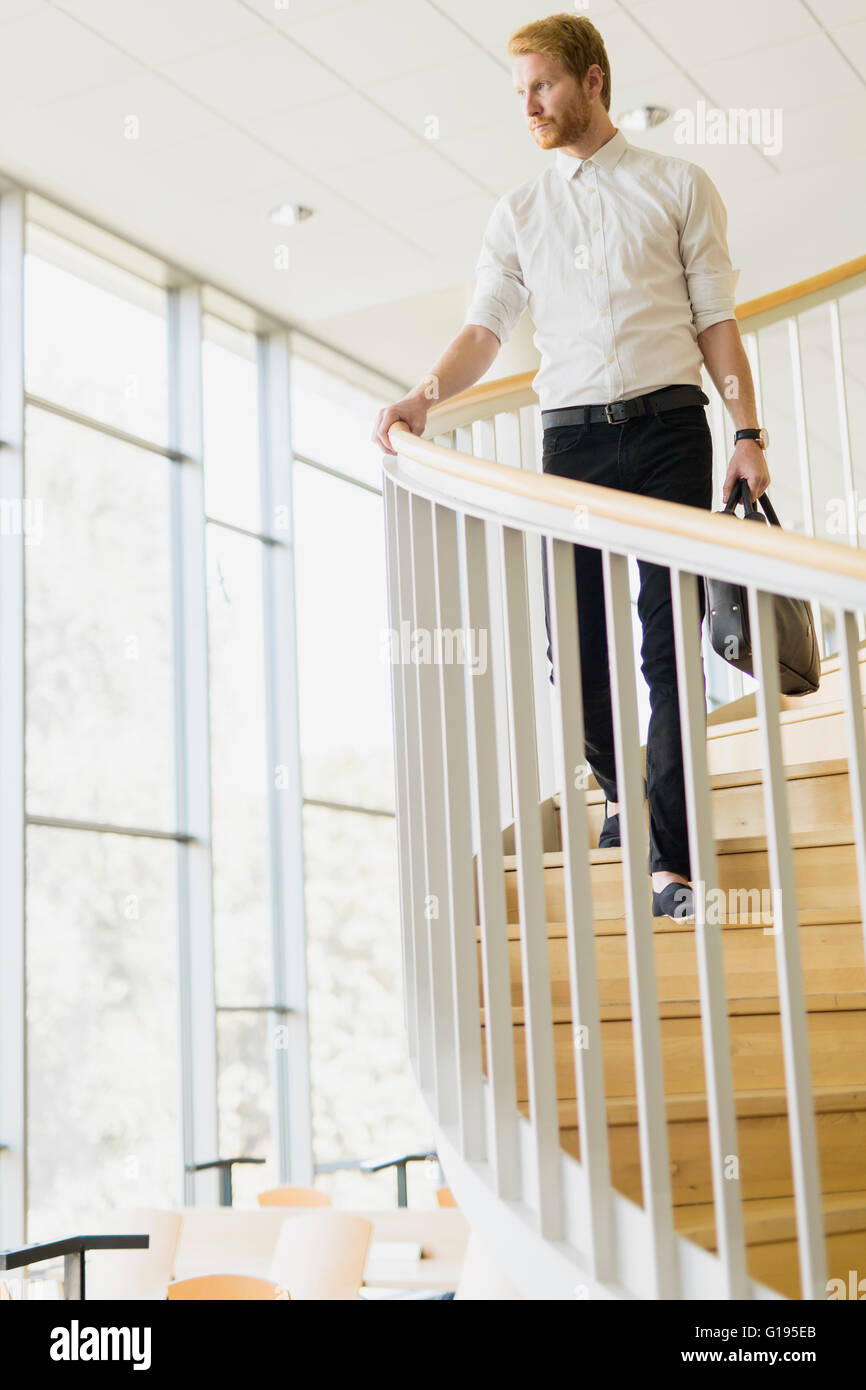 Handsome businessman walking down the stairs whilst holding a bag - Stock Image