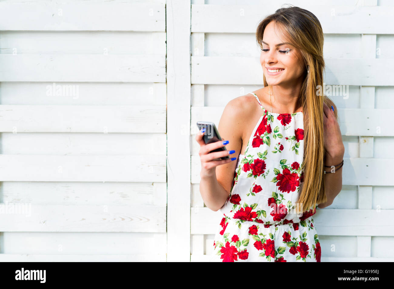 Beautiful young woman using phone while leaning against a white wall during a bright summer day Stock Photo