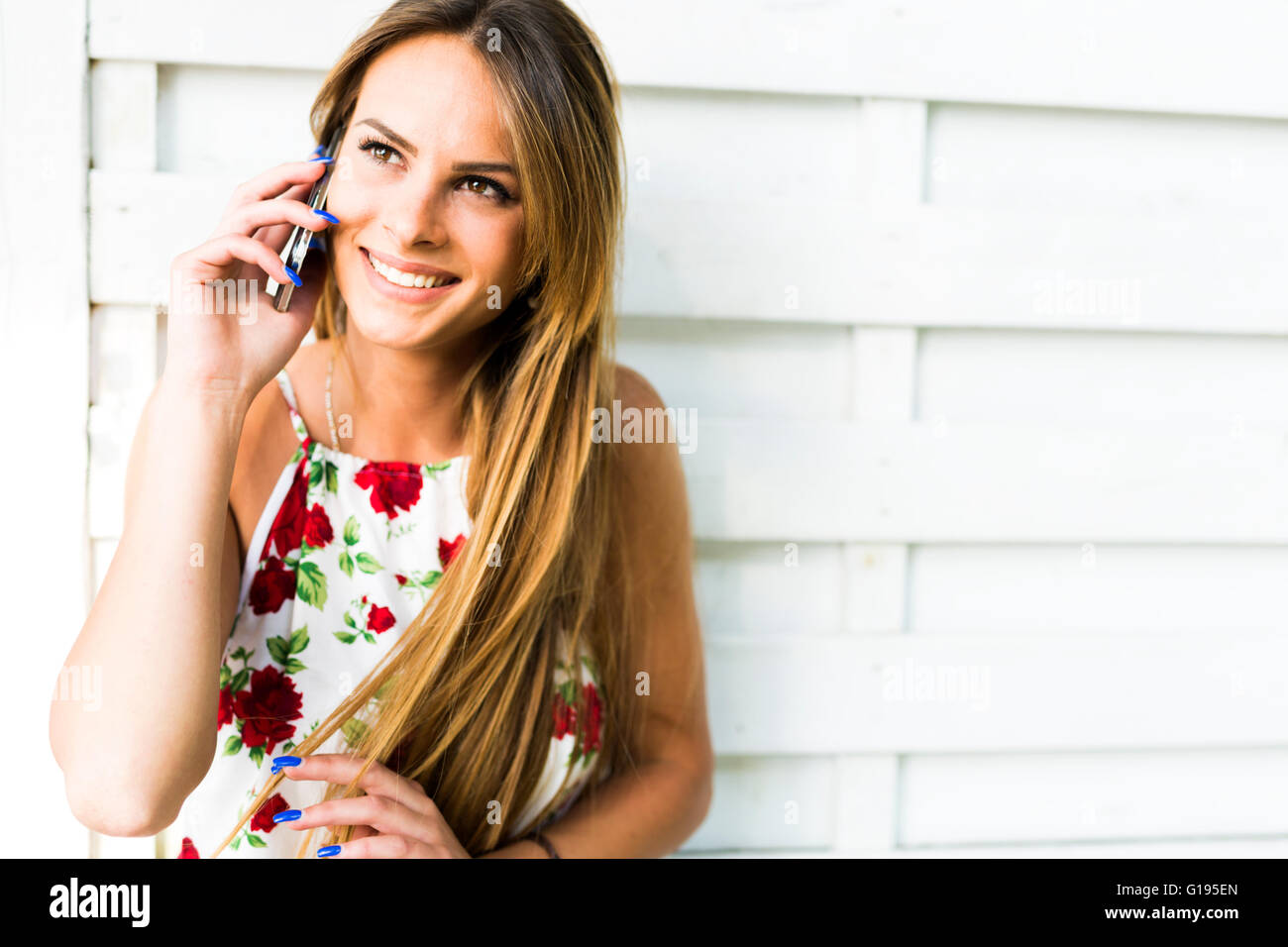Beautiful young happy woman smiling during a phone call while leaning against a white wall Stock Photo