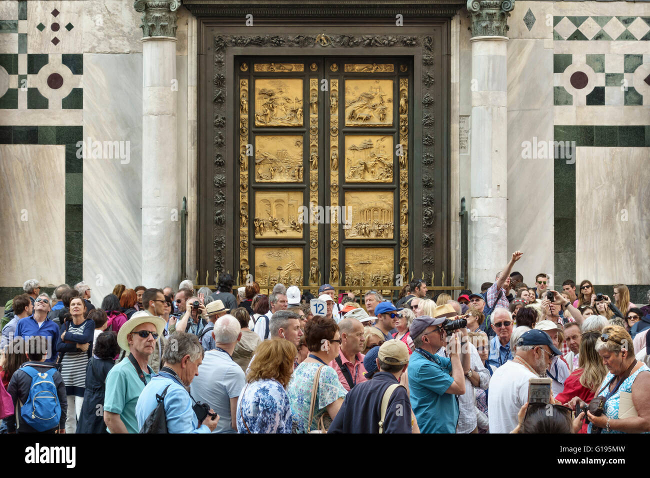 Florence, Italy. Crowds of tourists outside the Baptistery, in front of Ghiberti's famous bronze doors (the - Stock Image