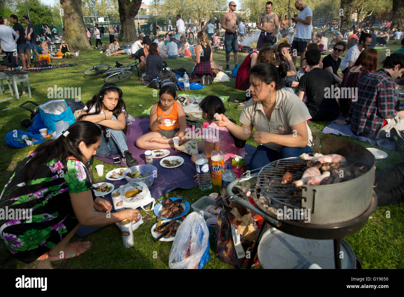 Hackney. London Fields park. Sunday afternoon in the sun. An Ecuadorian family have a barbecue . - Stock Image