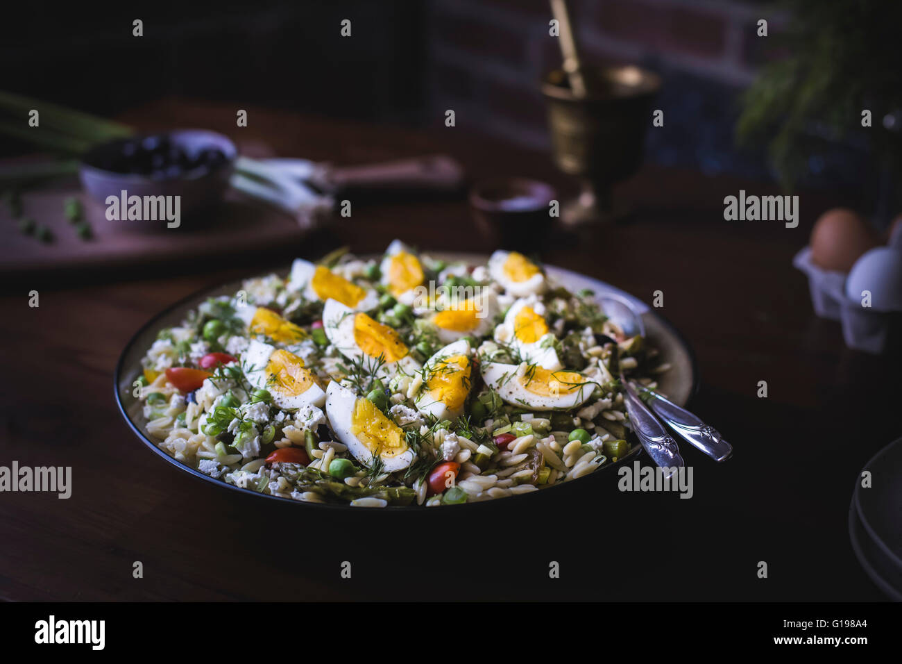 A large bowl of Mediterranean-Style Orzo Salad with Spring Vegetables is photographed from the front view. - Stock Image
