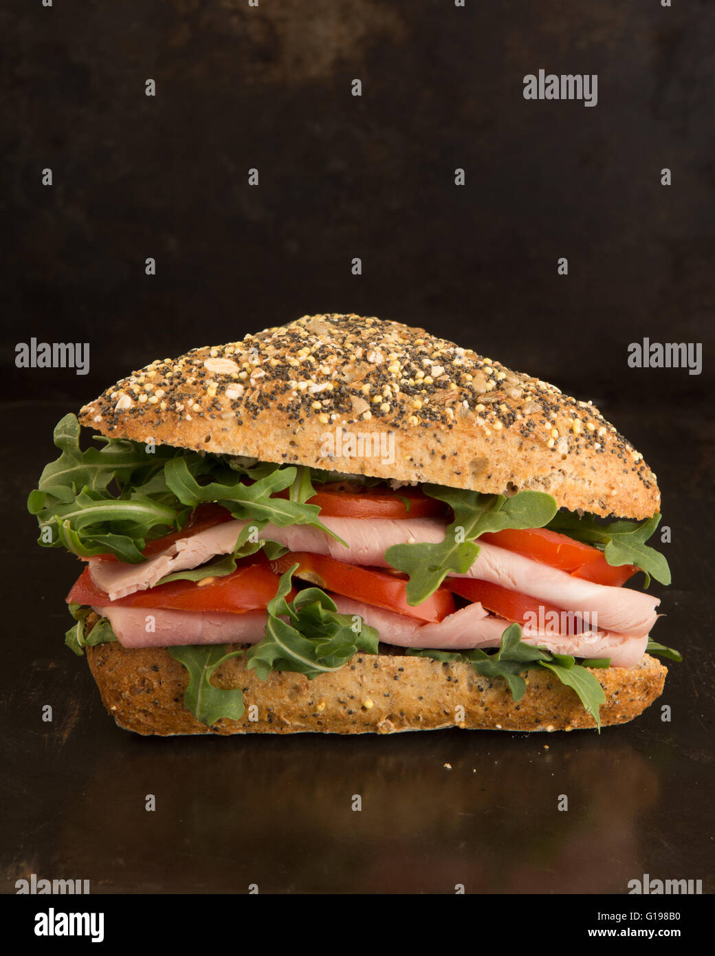 rustic ham salad sandwich in seeded bread roll against dark background - Stock Image