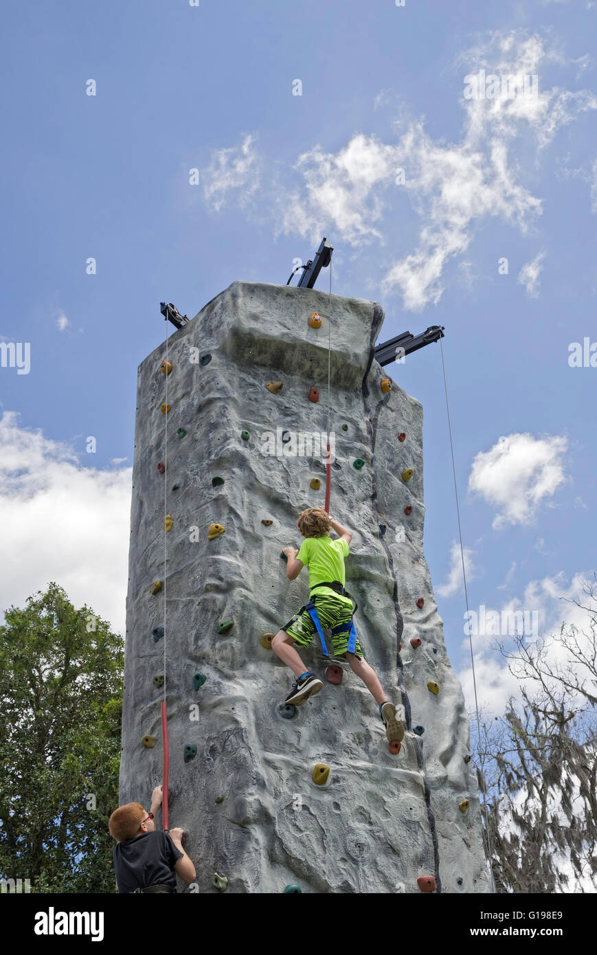 Trying to reach the top of a climbing wall and ring the bell signaling success.  At Pioneer Days annual celebration - Stock Image