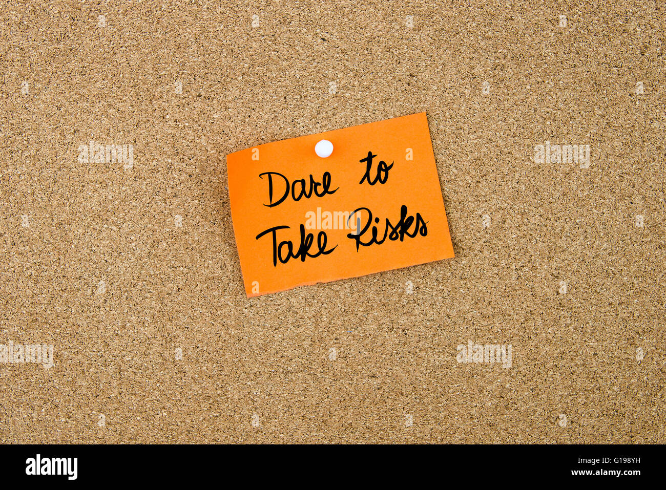 Dare To Take Risks written on orange paper note pinned on cork board with white thumbtacks, copy space available - Stock Image
