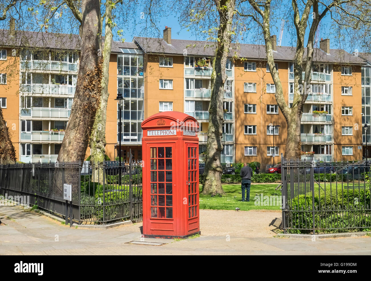 Traditional UK red telephone box located near block of flats in central London. - Stock Image