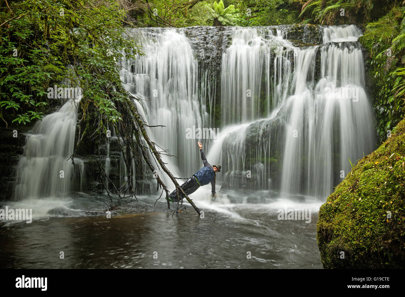 long exposure of man doing yoga pose side plank in a waterfall - Stock Image