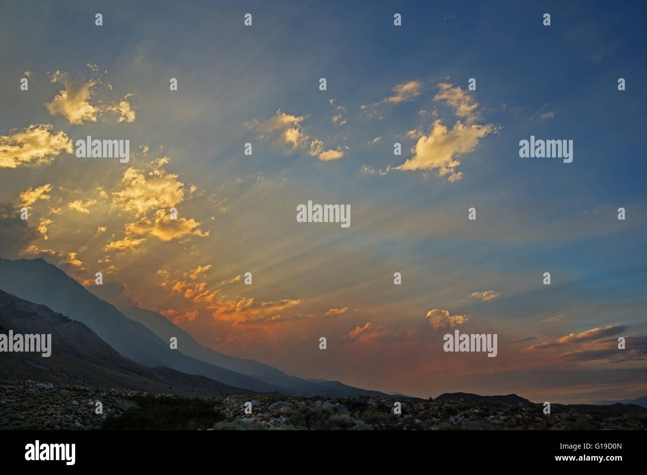 a smoky mountain sunset with sunrays spreading out over the valley - Stock Image