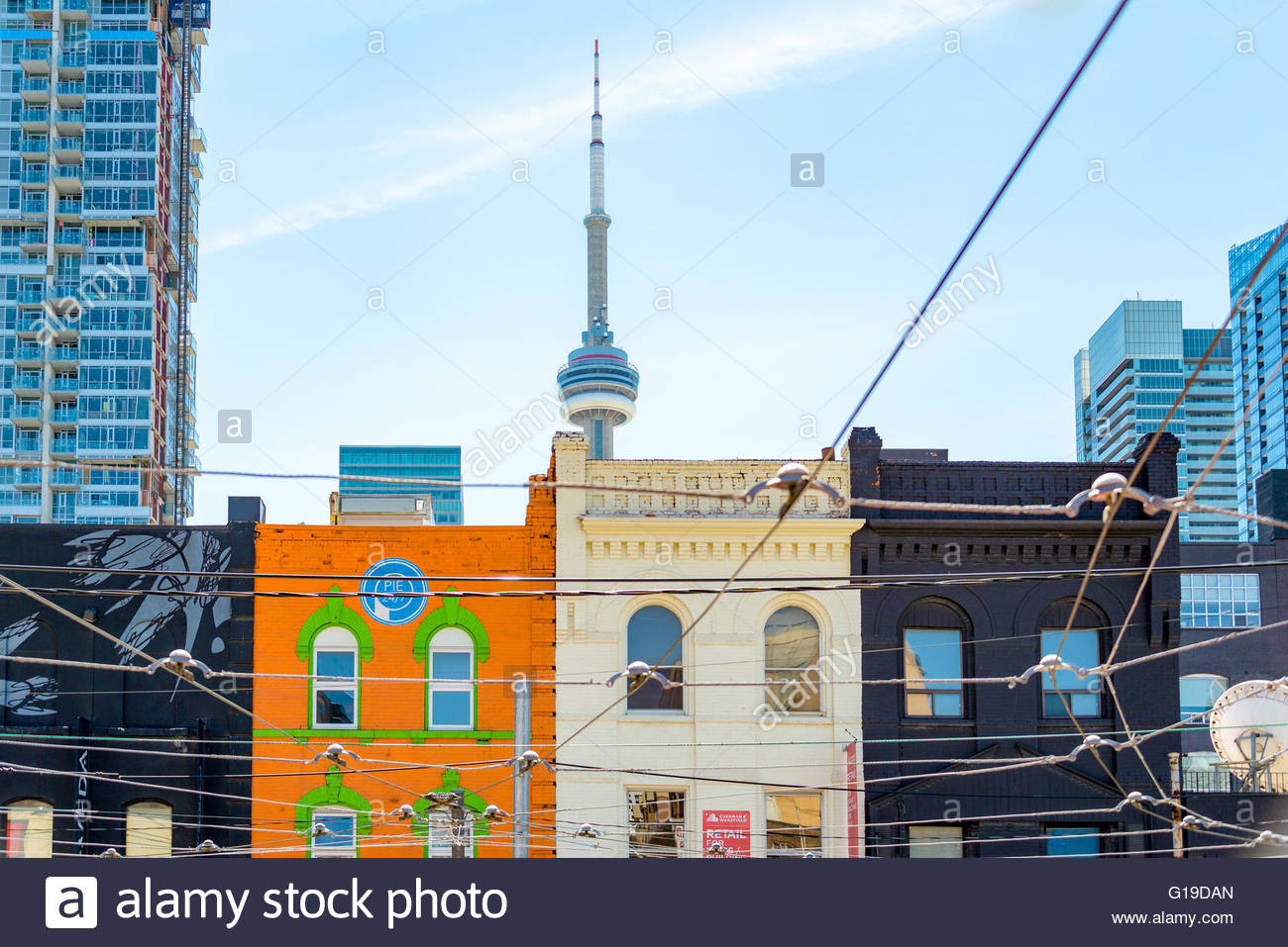 CN Tower and Victorian Houses: architectural contrast. The Tower is a symbol of Canadian history and a Landmark - Stock Image