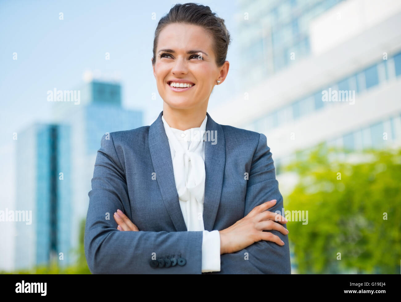 Into the ultra-modern business trends. Smiling business woman in modern office district looking into the distance - Stock Image