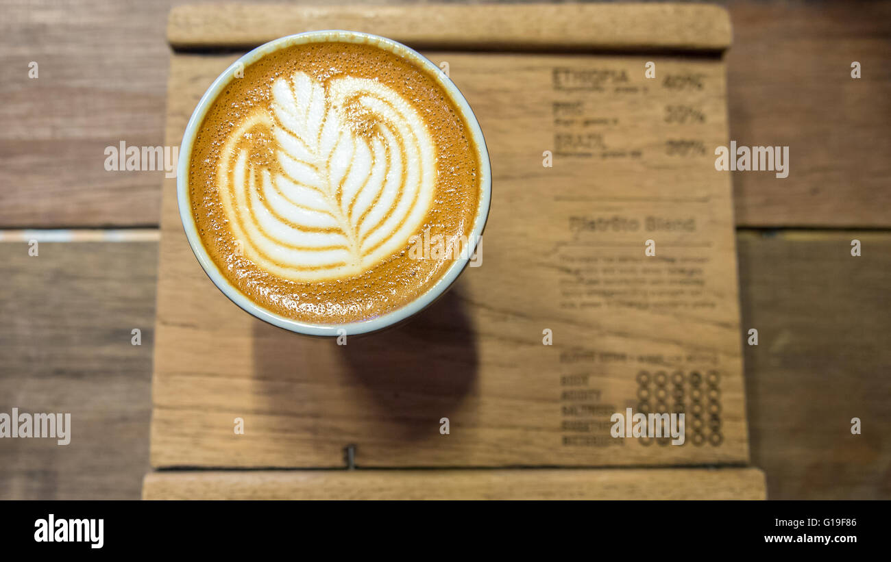 Coffee with white leaf latte art on wooden board - Stock Image
