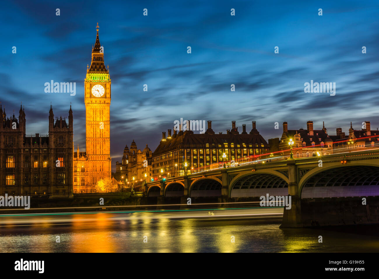 Long exposure after sunset capturing buses on Westminster Bridge and boats on the River Thames, London, UK. - Stock Image