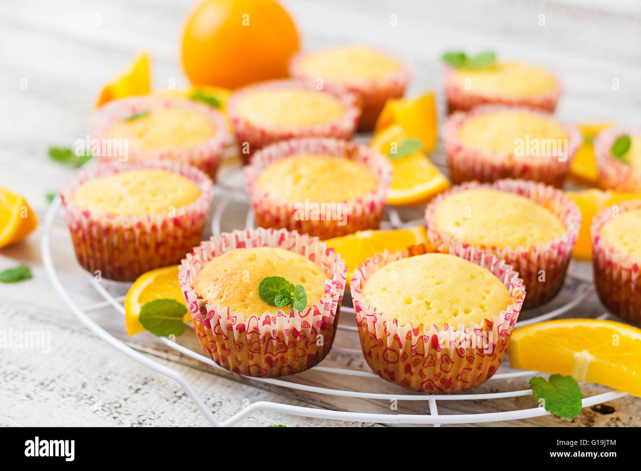 Tasty muffins with oranges and mint - Stock Image