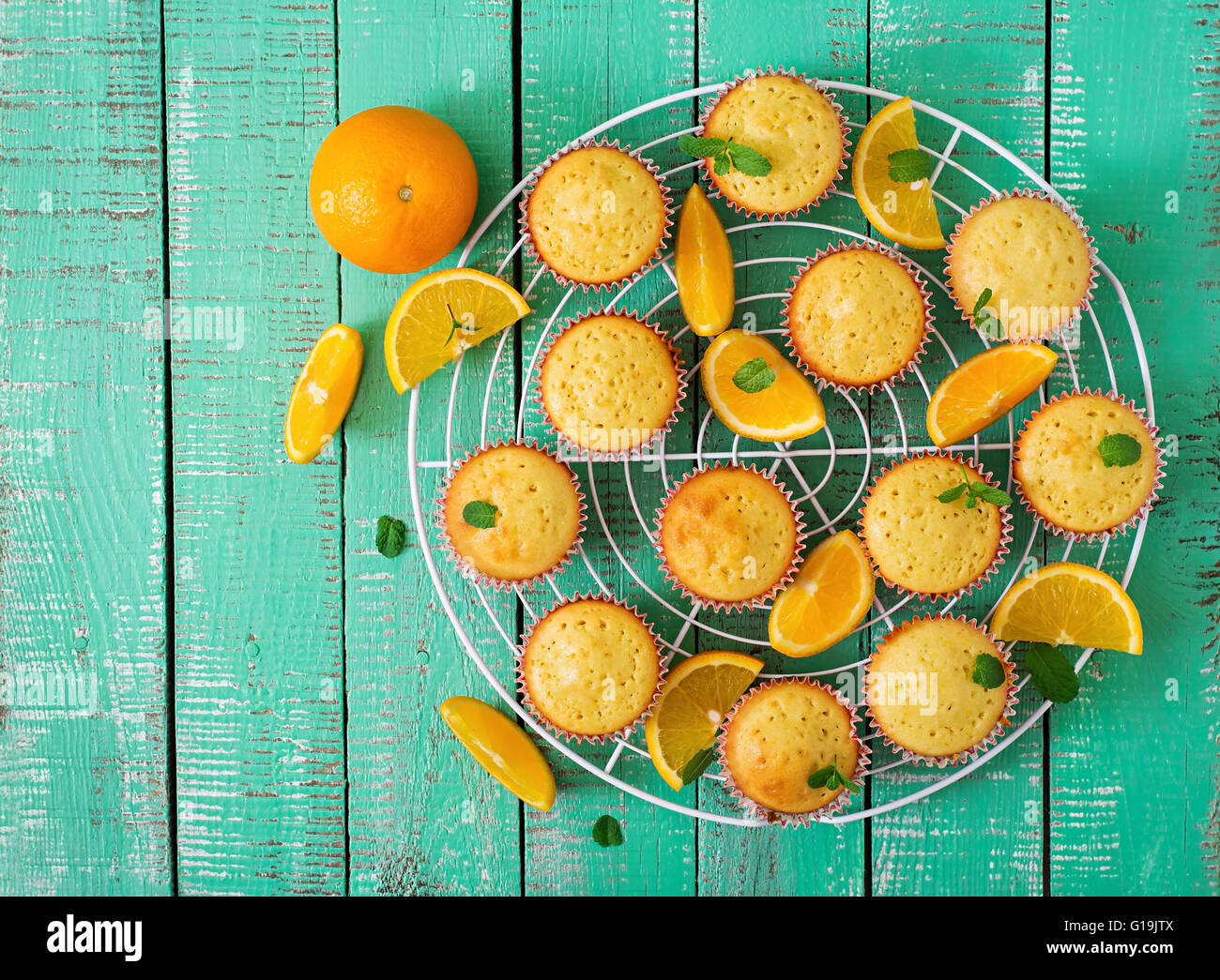 Tasty muffins with oranges and mint. Top view - Stock Image