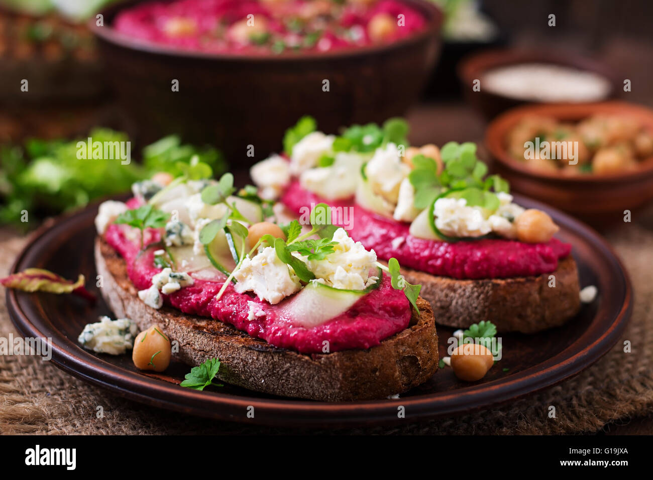 Vegan sandwiches with beetroot hummus, cucumber and blue cheese - Stock Image