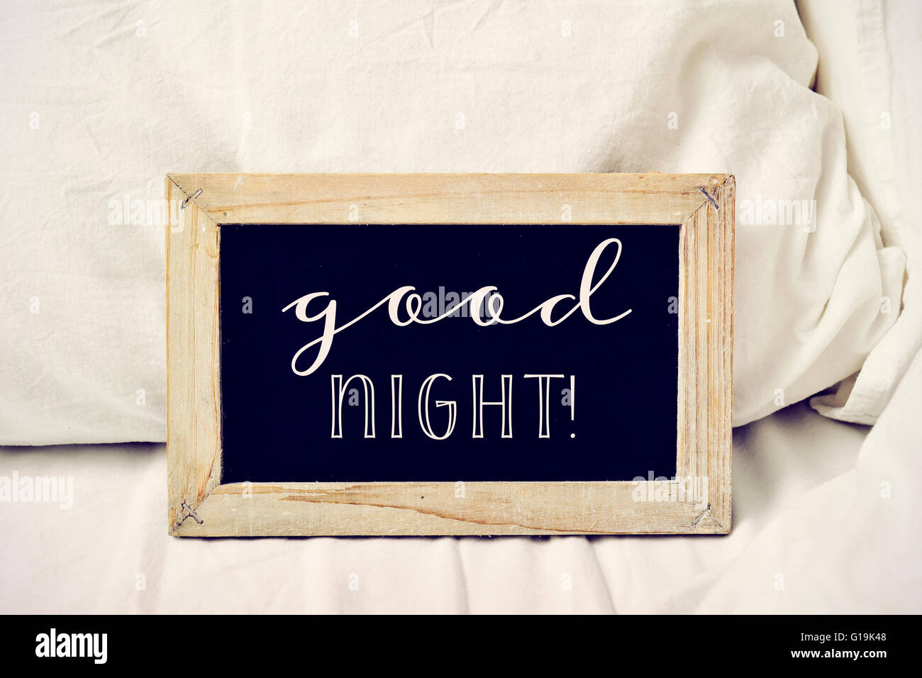 closeup of a wooden-framed chalkboard with the text good night written in it, placed on a comfortable bed - Stock Image