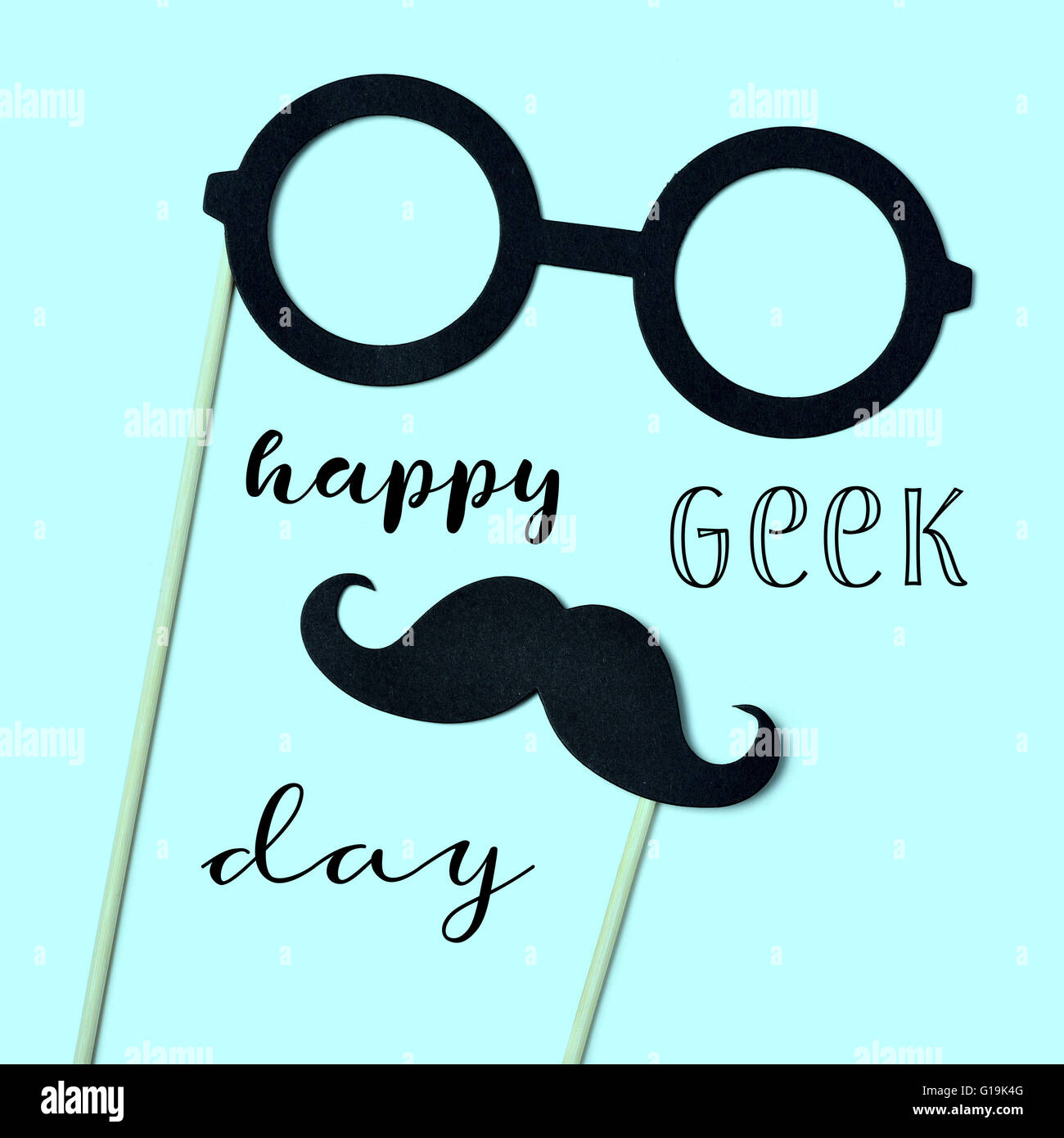 the text happy geek pride and a pair of round-framed eyeglasses and a mustache attached to handles depicting a man - Stock Image