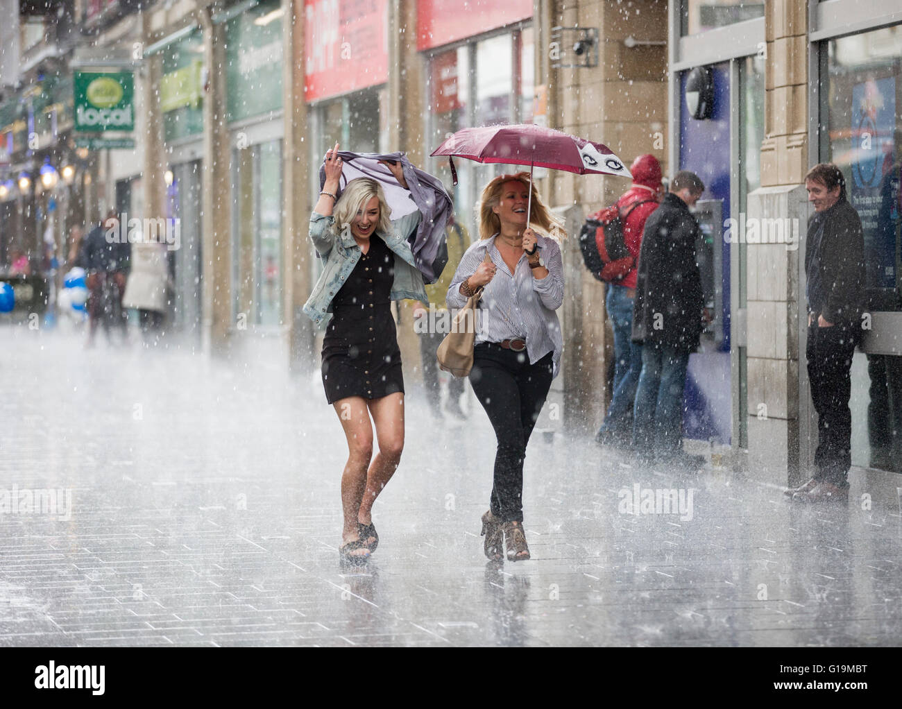 Two women running down a street in Leicester, UK, in a rainstorm. - Stock Image
