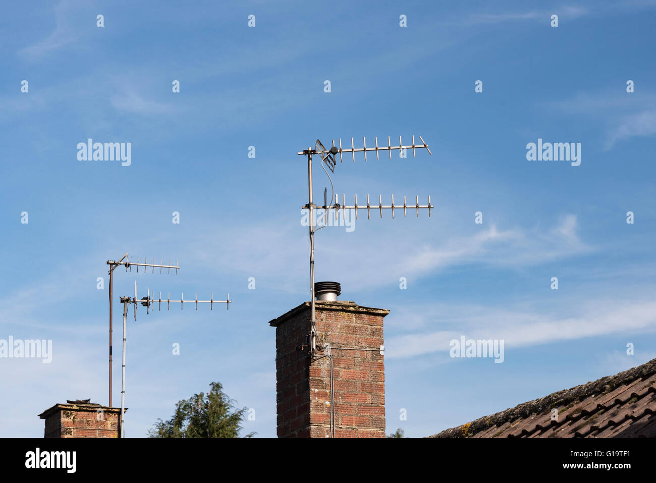 TV aerials on residential house chimney. - Stock Image