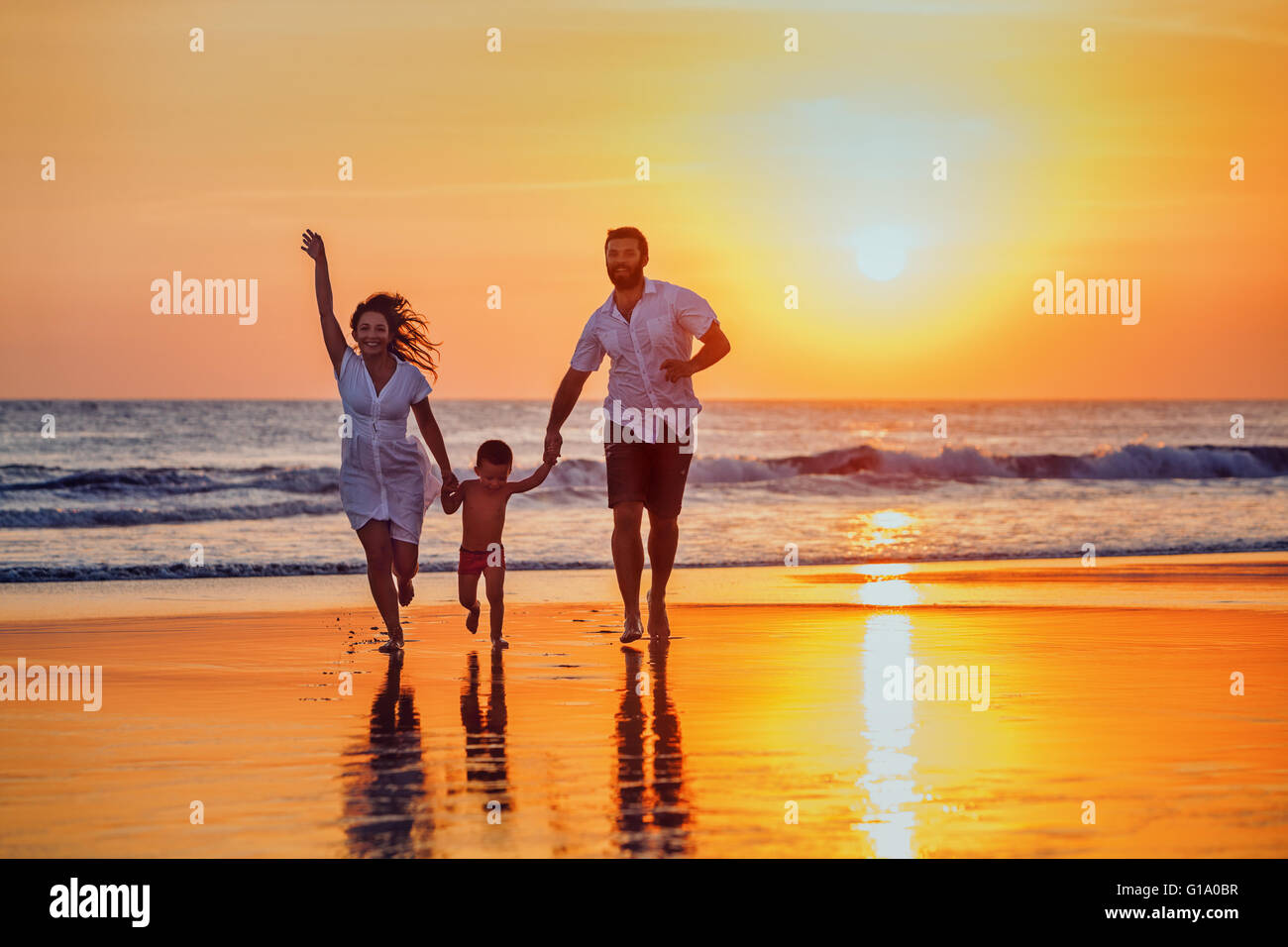 Happy family - father, mother, baby son hold hands and run with fun along sunset sea surf on black sand beach. - Stock Image