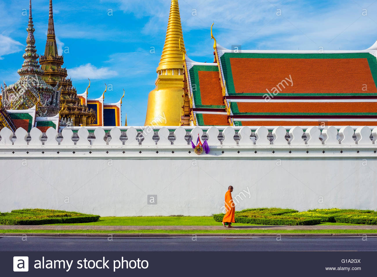 A monk passes in front of Wat Phra Kaew and the Grand Palace, Bangkok, Thailand - Stock Image