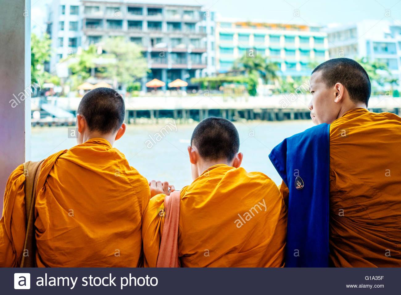 Three monks looking over the Chao Phraya River, Bangkok, Thailand - Stock Image