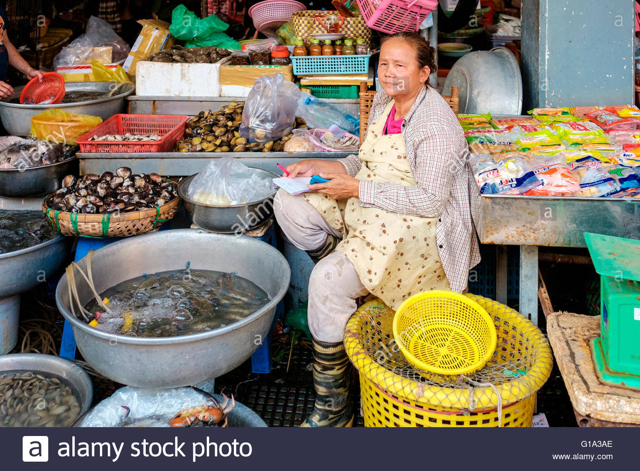 Woman in her stall selling fresh and live seafood at Central Market, Phnom Penh, Cambodia - Stock Image