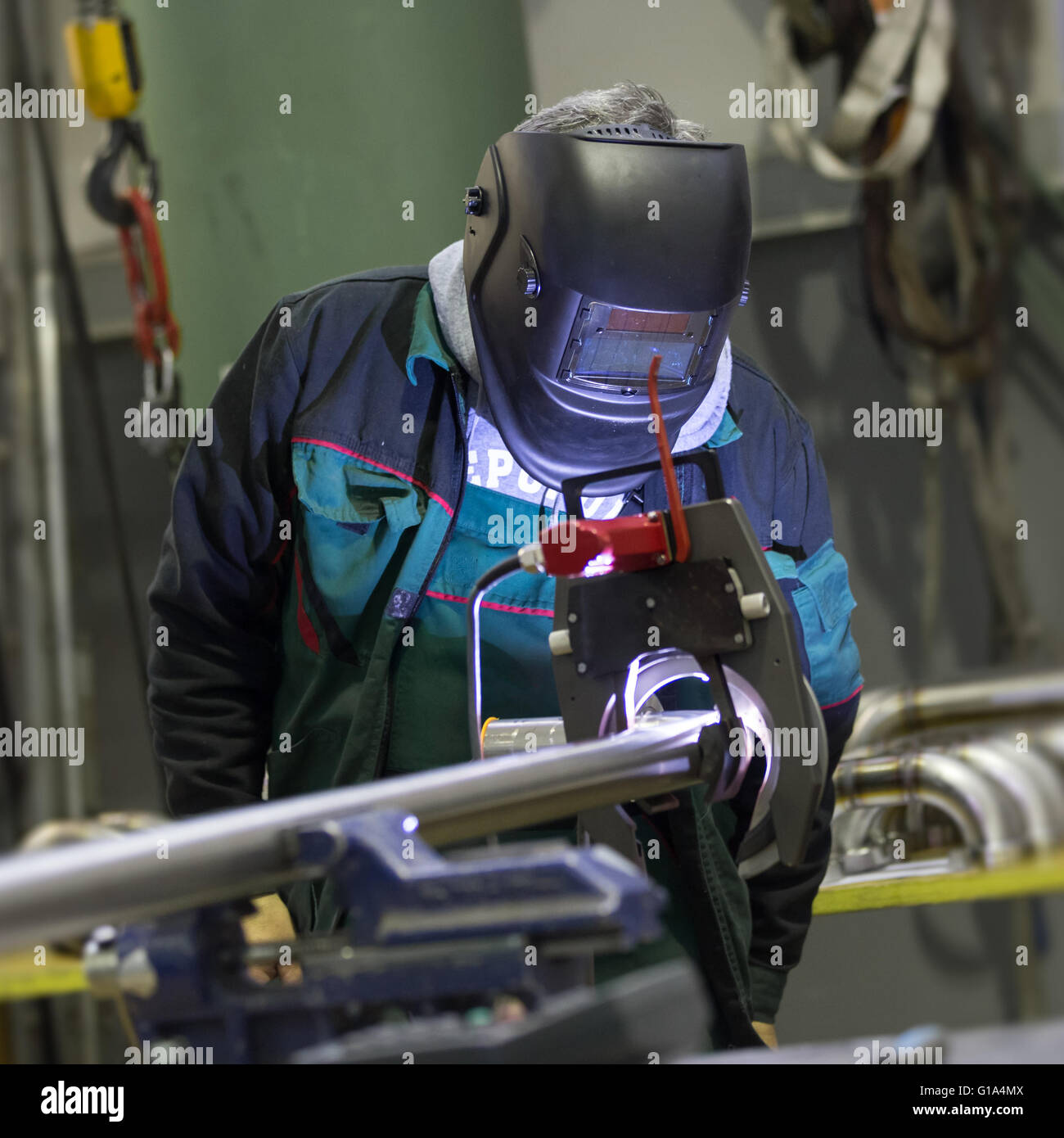 Industrial worker setting orbital welding machine. - Stock Image