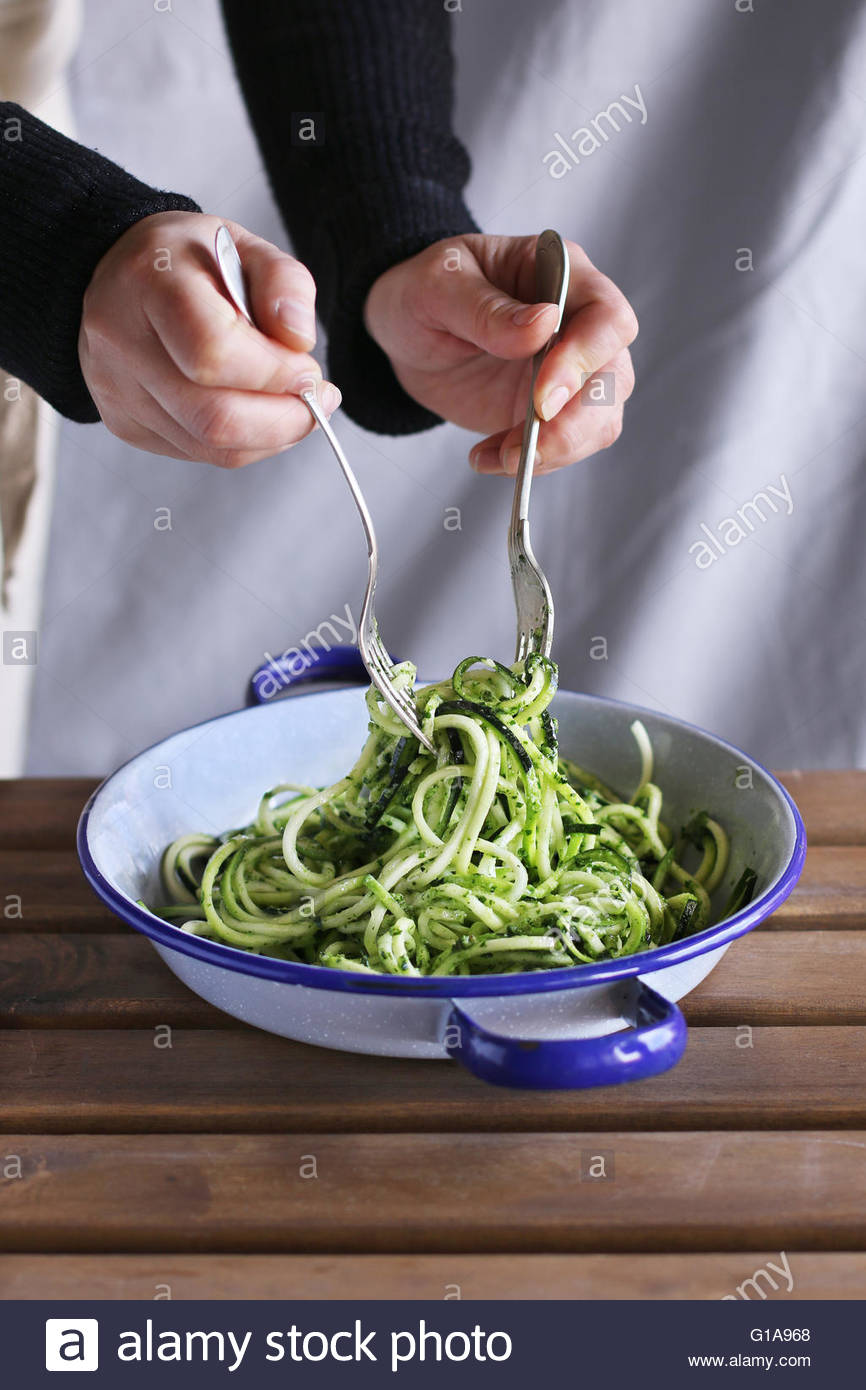 Female hands mixing zucchini noodles with pesto sauce. - Stock Image