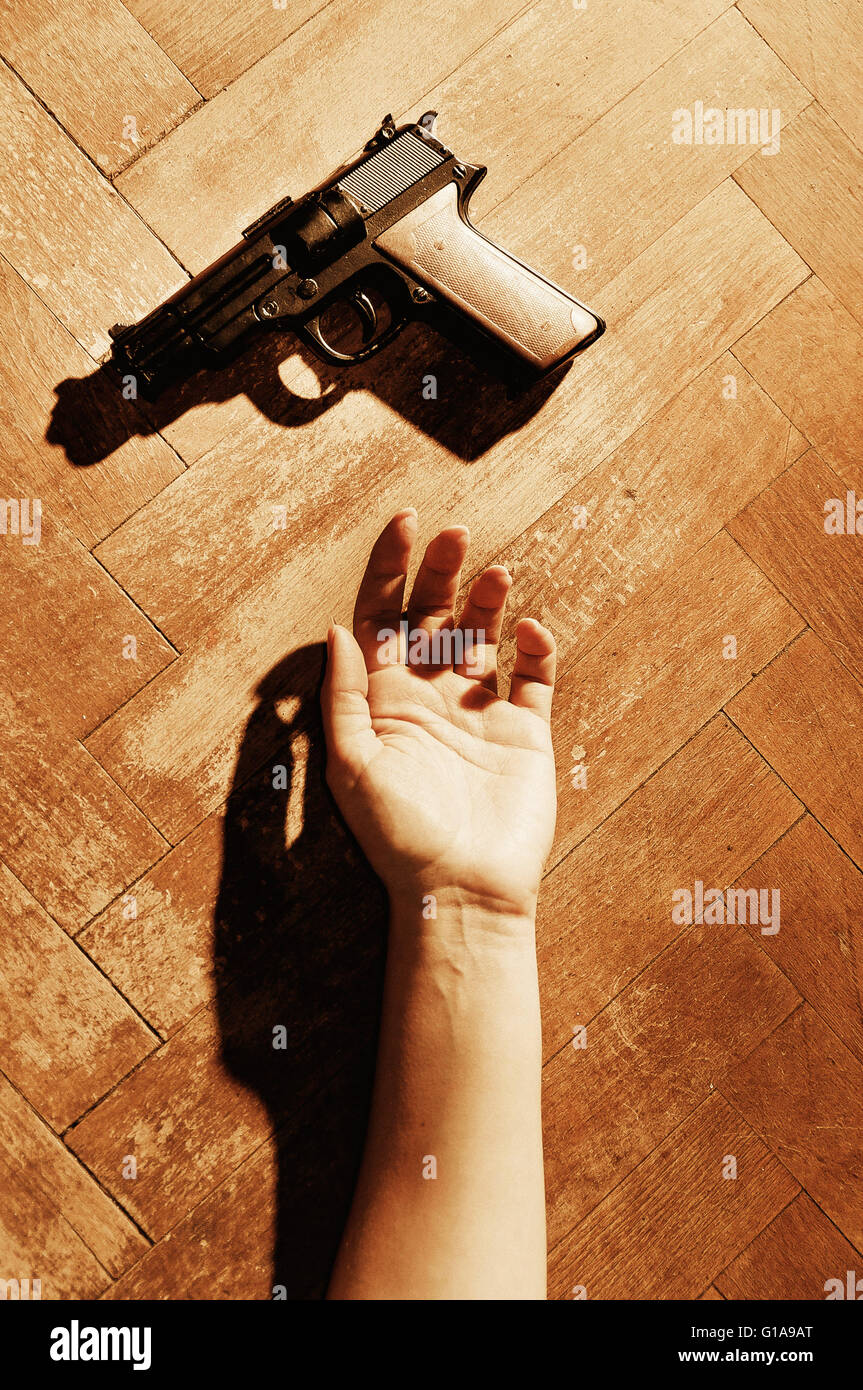 woman hand lying on the floor and a gun near her - Stock Image
