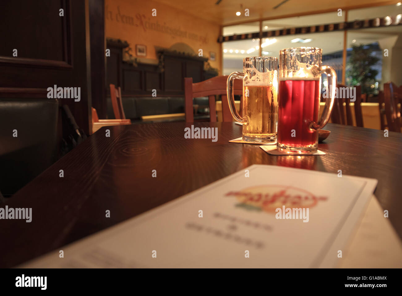 2 beer mugs on a romantic table in a restaurant in Berlin Germany - Stock Image