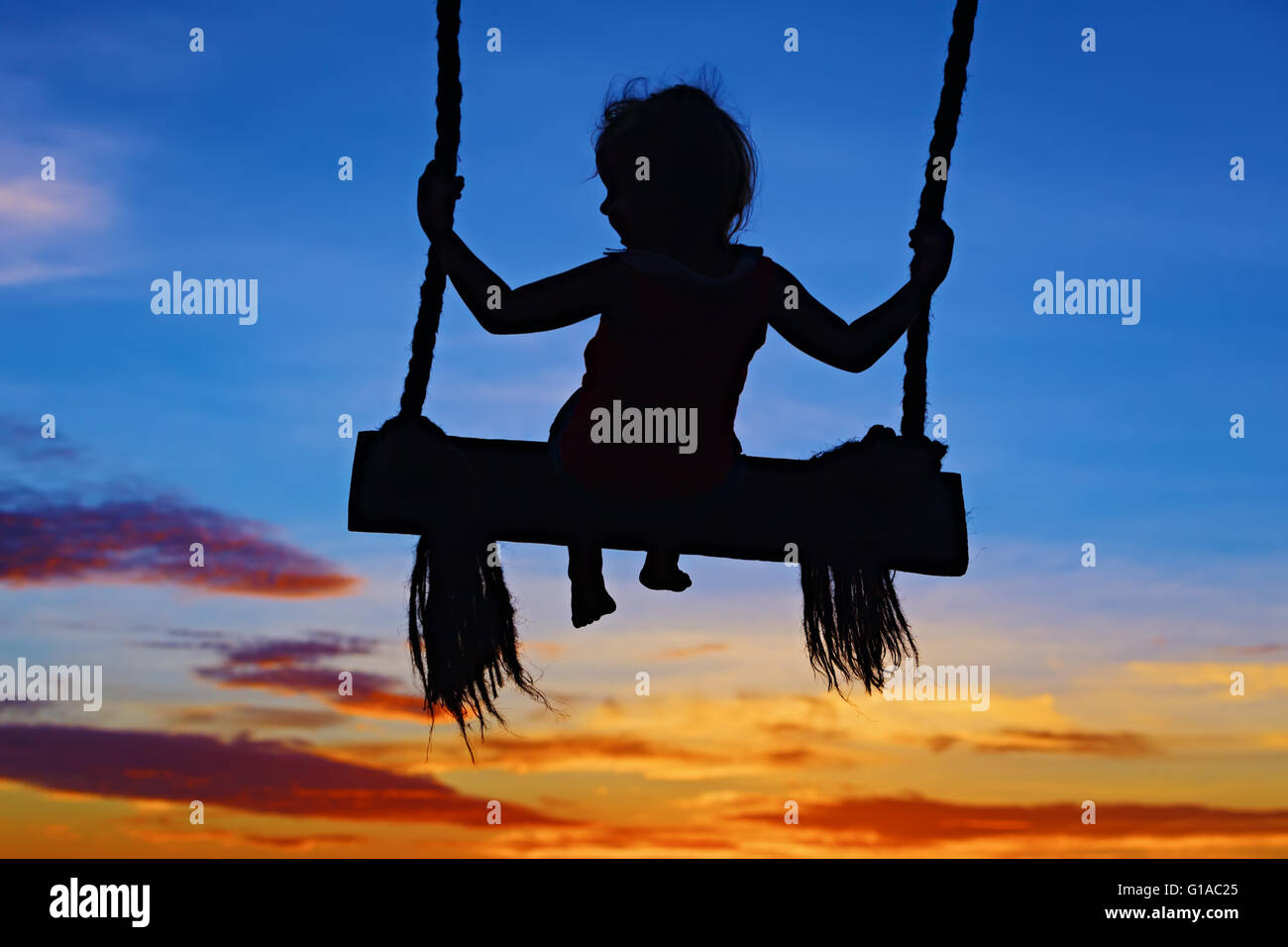 Black silhouette of baby girl flying high with fun on rope swing on blue orange sunset sky background. - Stock Image