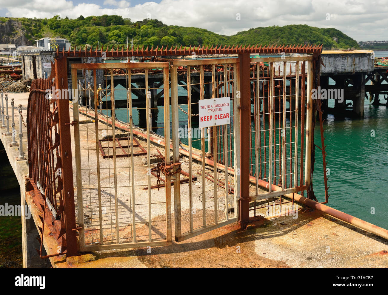Rusty gates and fencing around a dangerous structure. - Stock Image