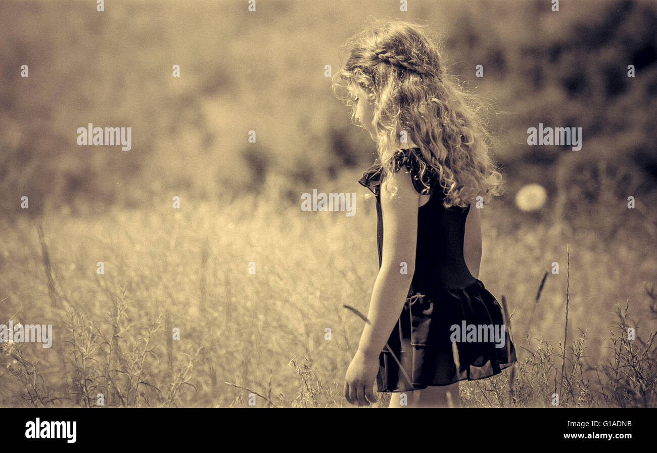 image of a young girl with beautiful braided hair taking a walk amongst tall grasses enjoying the solitude - Stock Image