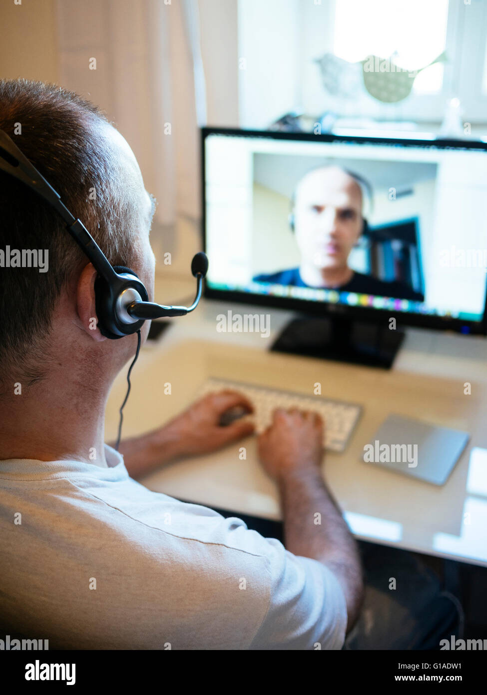 Teleworker in home office having a video conference with a colleague. - Stock Image