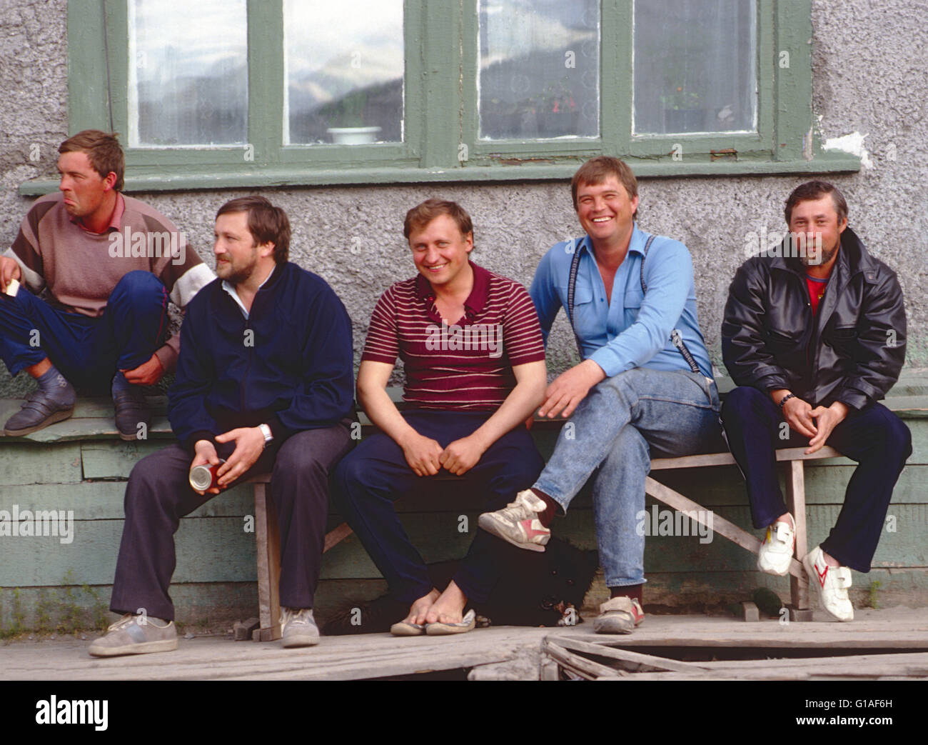 LOCAL MEN RELAX ON OUTDOOR BENCH; EGVEKINOT, MAGADAN REGION; COASTAL TOWN ON BERING SEA; RUSSIAN FEDERATION - Stock Image