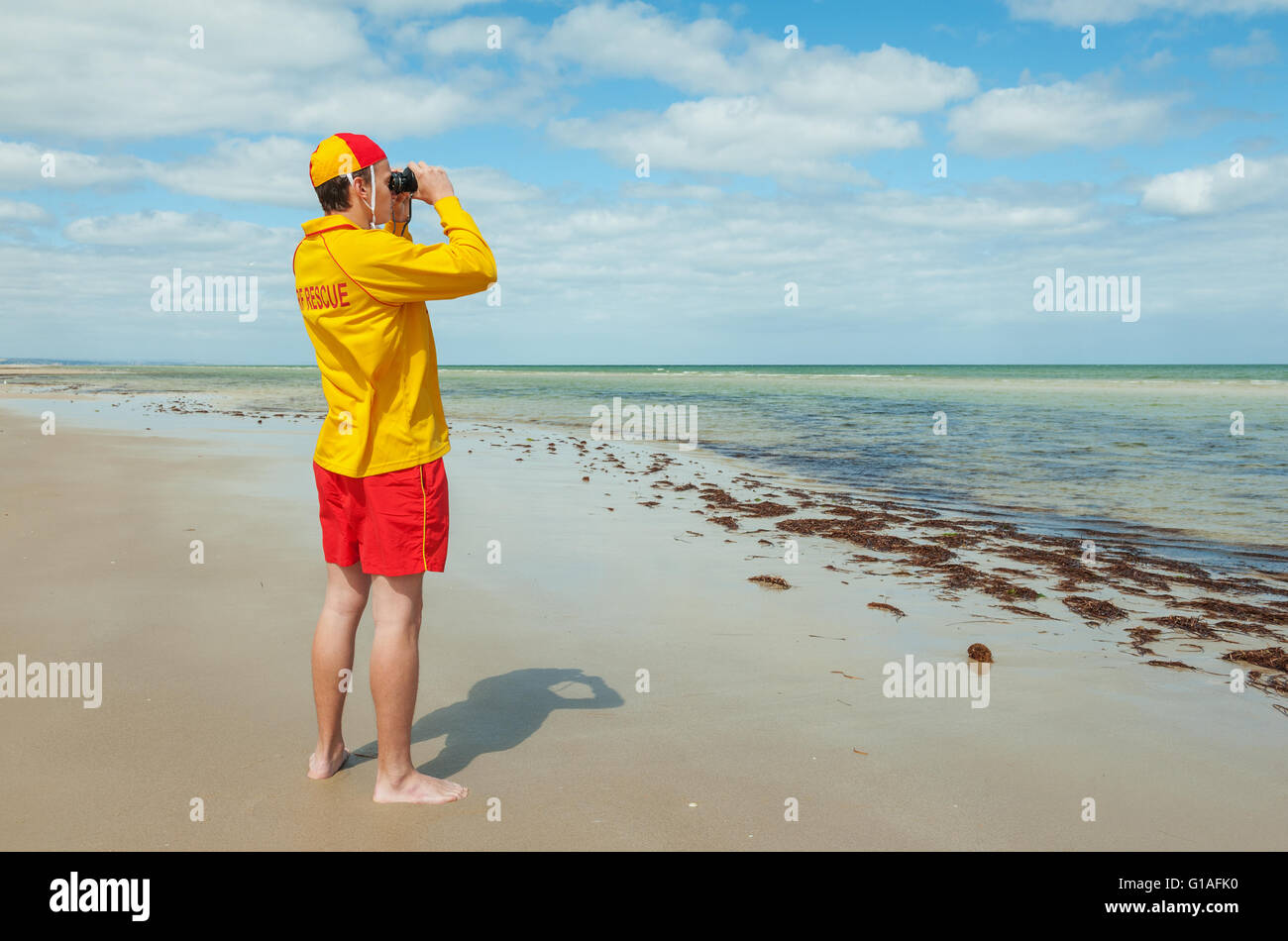 young man  life saver  watching the situation on the sea - Stock Image