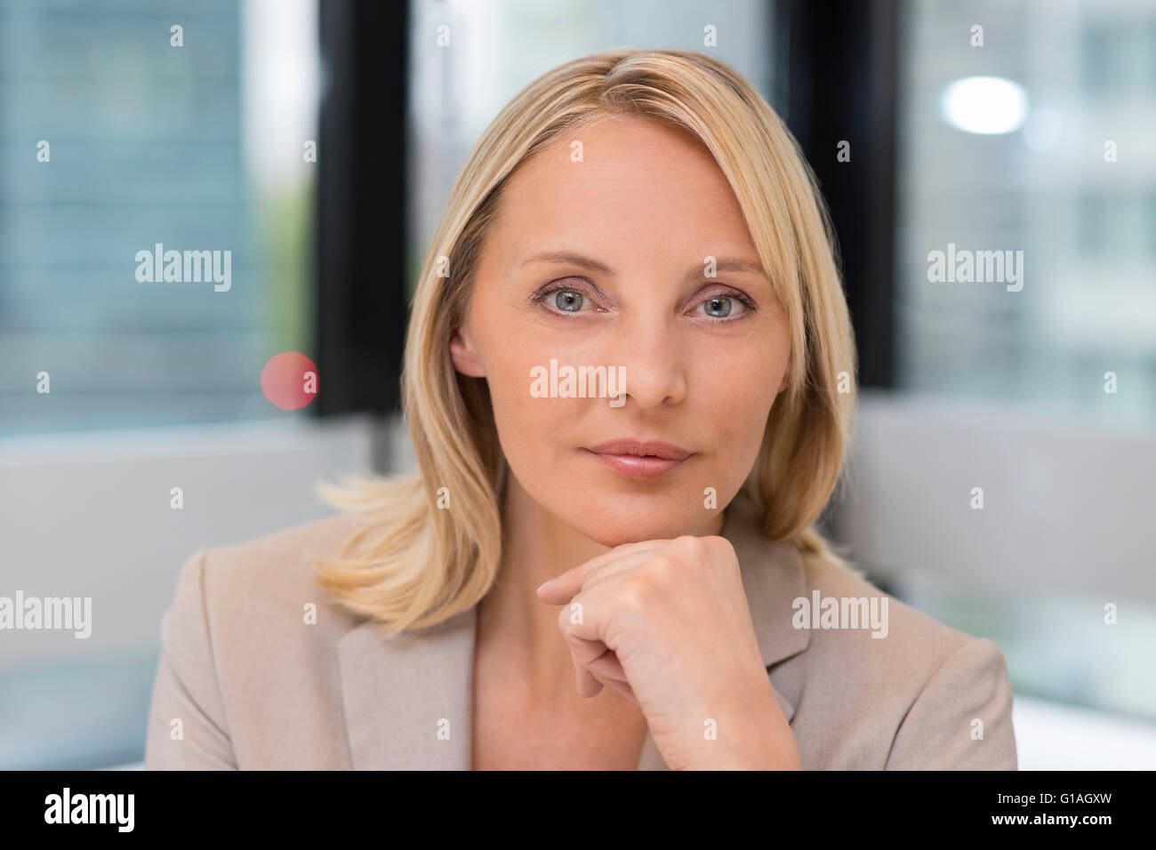 Portrait of businesswoman in modern office. Building in background. Looking at camera Stock Photo
