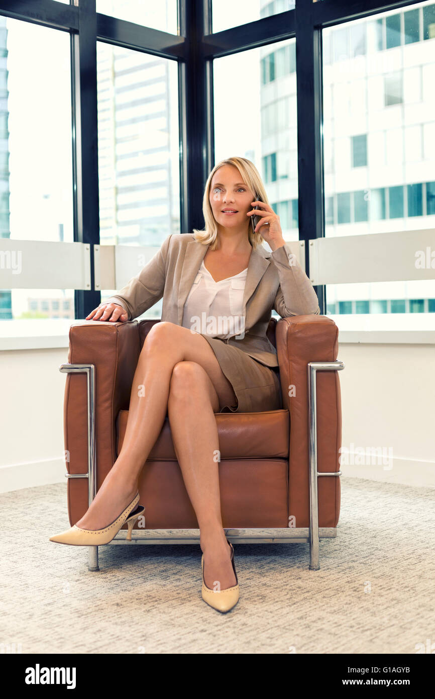 Cheerful business woman sitting in a chair. on mobile phone in modern office - Stock Image