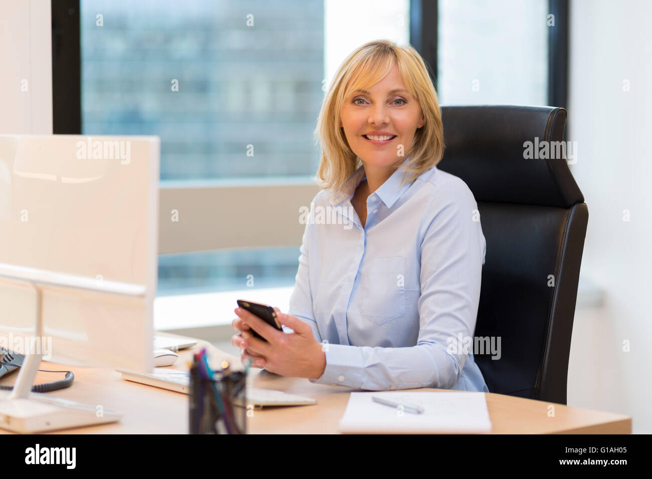 Smiling Middle aged business woman working in modern office. Looking at camera Stock Photo