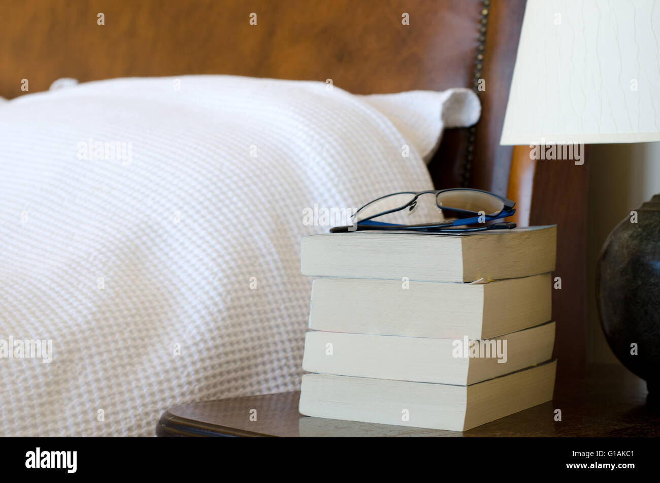 Pile on books with reading glasses on bedside table - Stock Image
