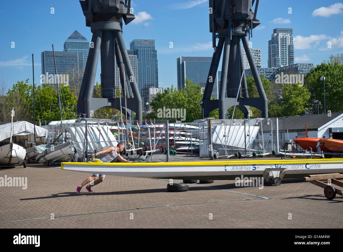 Man repairing boat at the Docklands Sailing and Watersports Centre near Canary Wharf, London, UK - Stock Image