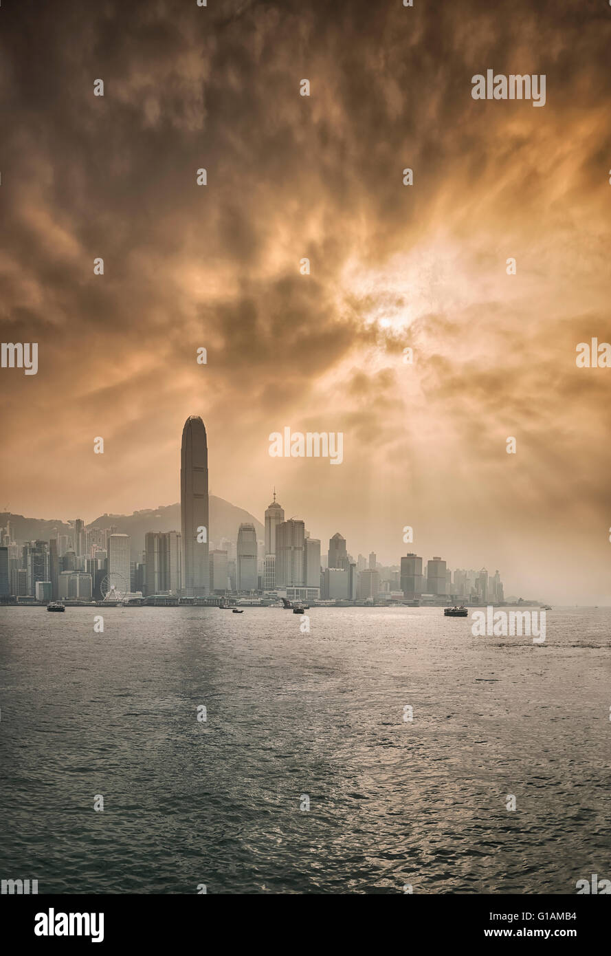 Skyline of Central, Hong Kong Island and Victoria Harbour with sun shining behind dramatic clouds, Hong Kong, China, - Stock Image