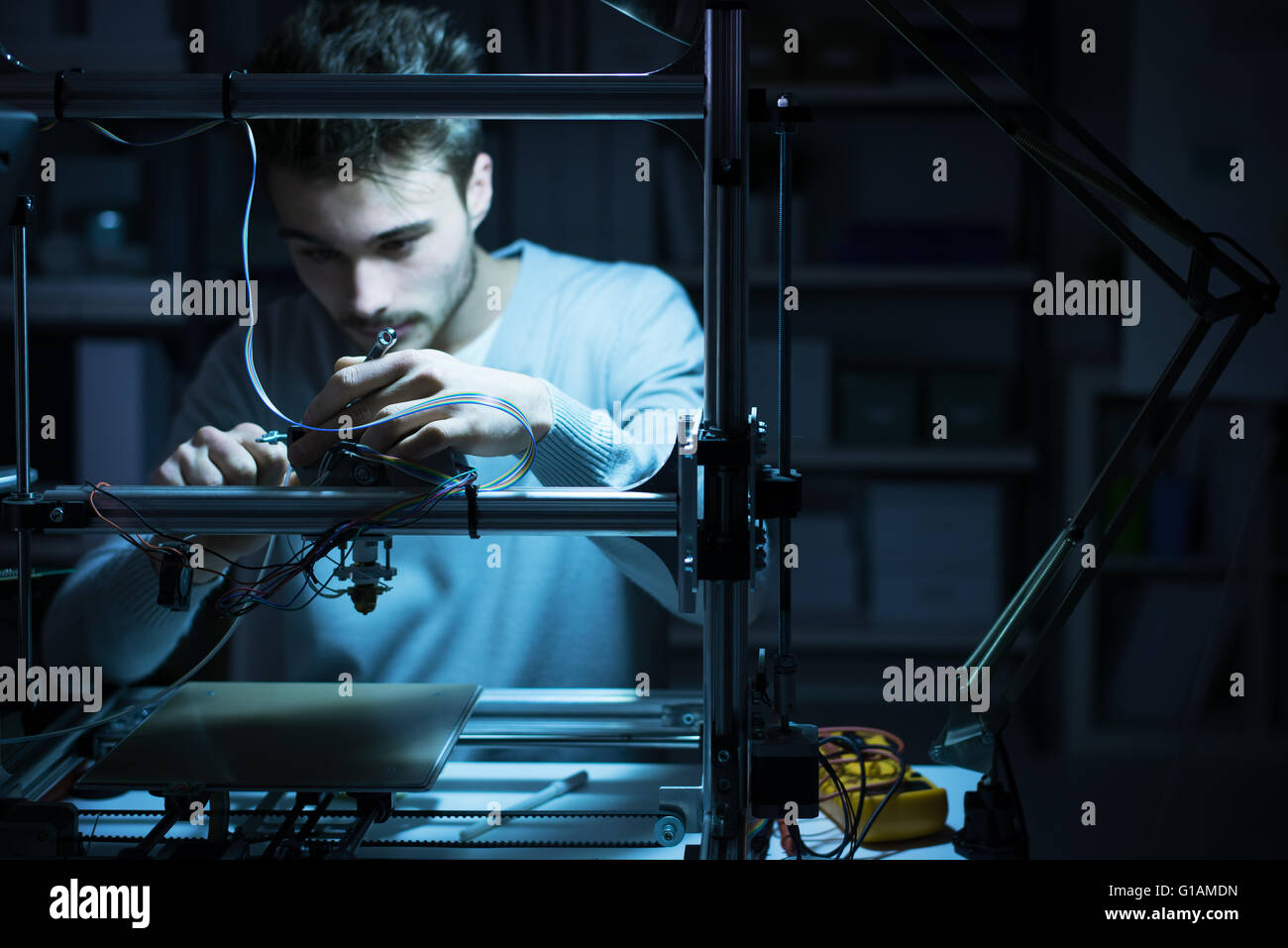 Young engineer working at night in the lab, he is adjusting a 3D printer's components, technology and engineering - Stock Image