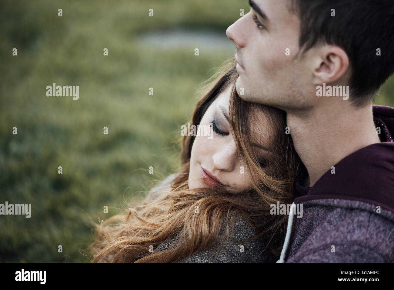 Young loving couple relaxing on grass and hugging, she is smiling and leaning on his shoulder, relationships and - Stock Image