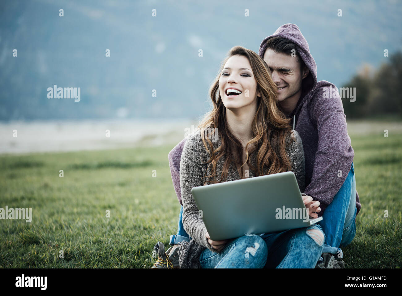 Playful young couple sitting on the grass outdoors, hugging and social networking with a laptop, love and relationships - Stock Image