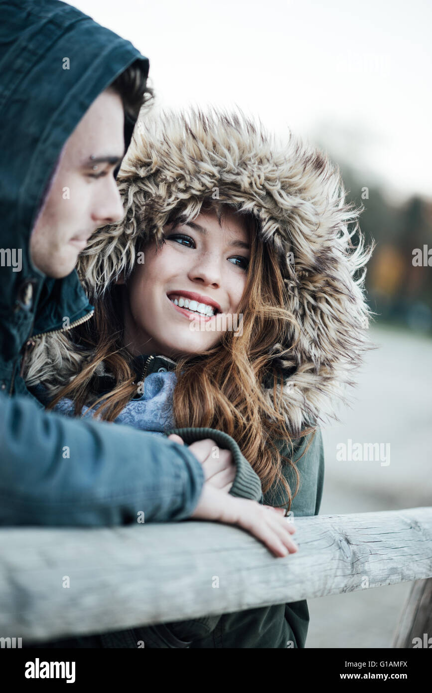 Smiling loving couple with hoods dating during a cold winter day, love and relationships concept - Stock Image